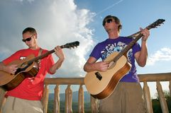 Guys Playing Guitar. Two friends letting the notes fly together with their guitars stock photos