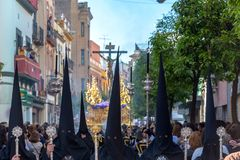 Guys in Pointy Hats. SEVILLE, SPAIN - MARCH 27: People wearing black hoods in a Holy Week procession in Seville, Spain on March 27, 2018 stock image