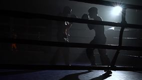 Guys preparing for a kickboxing competition. Silhouette. Slow motion
