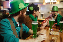 Guys in pub. Guys in green hats relaxing in pub and having beer Royalty Free Stock Photos