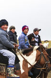 Guys ride horse at Song Kul Lake in Kyrgyzstan Stock Images