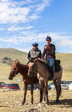 Guys ride horse at Song Kul Lake in Kyrgyzstan Stock Photo