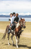 Guys ride horse at Song Kul Lake in Kyrgyzstan Royalty Free Stock Photos