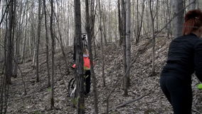 Guys ride in the woods on a bike stock footage