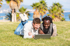 Guys sharing computer in grass. Caucasian and black boys lying on the grass looking at a computer Stock Photos