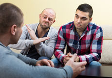 Guys sharing problems at the table. Guys sitting at the table and sharing the problems Stock Photo