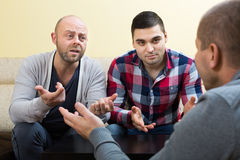 Guys sharing problems at the table Royalty Free Stock Photos