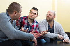 Guys sharing problems at the table. Three serious guys sitting at the table at home and sharing the problems Royalty Free Stock Photos