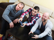 Guys sitting with joysticks Stock Images