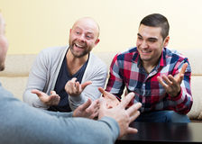 Guys sitting at table. Chatting and smiling at home Stock Photos