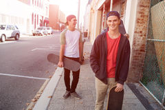 Guys skateboarders in street Stock Photography