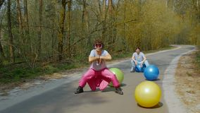 Guys street dancers in the forest. Young men street dancers in goggles with colorful balls in the forest. Happy guys in bright ski suits dance among of bright stock video