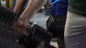 Guys taking and putting back heavy dumbbells to stand in gym, muscles training. Stock footage stock footage