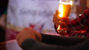 Guys talking in the pub, guy takes a sip of beer and puts it back on the bar counter. Only hands shown stock video footage