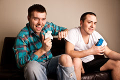 Guys Video Games Fun. Two attractive guys having fun while playing video games Royalty Free Stock Image