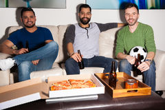 Guys watching a soccer game at home. Three attractive Latin guys relaxing at home and watching a soccer game while drinking beer and eating pizza at night Royalty Free Stock Photo