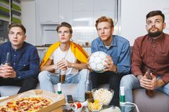 Men watching sport on tv together at home holding ball Stock Photography