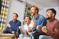 Men watching sport on tv together at home shouting happy royalty free stock photography
