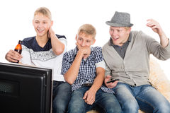 Guys watching your favorite show on TV. Group of young guys watching your favorite show on TV. Two of the boys twin brothers Royalty Free Stock Photography