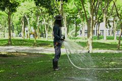 Guys are watering the lawn in the park. stock photography