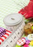 Guziki, kolorowe tkaniny, pomiarowa taśma, szpilki poduszka, naparstek Obrazy Royalty Free