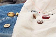 Guziki, szpilki i igły z niciami na, bawełnie i cajgu odzieżowym zbliżeniu obraz stock