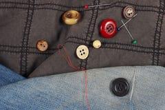 Guziki, szpilki i igły z niciami na, czarnej bawełnie i błękitnym drelichowym zbliżeniu obraz stock