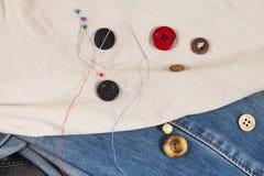 Guziki, szpilki i igły z niciami na, kanwie i cajgu odzieżowym zbliżeniu fotografia royalty free