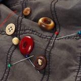 Guziki, szpilki i igły z niciami na tle bawełien ubrania, zamykają up obraz royalty free