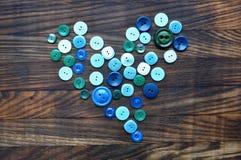 Guziki w kształcie serce na drewnianym tle Zdjęcia Royalty Free