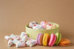 Gåvaask av muffin och färgglade Macaron på beige bakgrund, Fotografering för Bildbyråer
