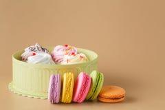 Gåvaask av muffin och färgglade Macaron på beige bakgrund, Royaltyfria Bilder