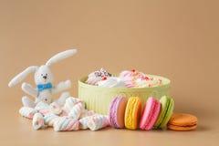 Gåvaask av muffin och färgglade Macaron på beige bakgrund, Arkivbilder