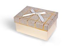 Den beige gåvan boxas med guld- band- och vitpilbågeisolator Royaltyfri Bild