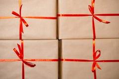 Gåvor i brunt papper som binds med ett rött band Arkivfoto
