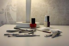 Gwóźdź poleruje z manicure instrumentami na białym stole Zdjęcia Stock
