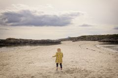 Child running across the sand stock photography
