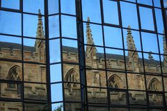 Glasgow gothic style church reflected in the windows of modern buildings. Gothic Architecture in reflected in the windows of a modern building in Glasgow city royalty free stock image