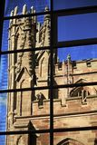Glasgow gothic style church reflected in the windows of modern buildings. Looking up at gothic church Architecture in reflected in the windows of a modern royalty free stock photos