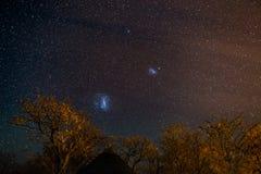 Gwiaździsty niebo i majestatyczne Magellanic chmury schwytani w Afryka, outstandingly jaskrawy, Akacjowi drzewa i słomiana buda w Obraz Royalty Free