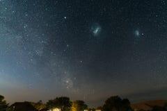 Gwiaździsty niebo i majestatyczne Magellanic chmury schwytani w Afryka, outstandingly jaskrawy, Akacjowi drzewa i słomiana buda w Zdjęcia Royalty Free