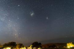 Gwiaździsty niebo i majestatyczne Magellanic chmury schwytani w Afryka, outstandingly jaskrawy, Akacjowi drzewa i słomiana buda w Zdjęcia Stock