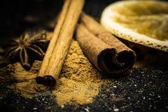 Gwiazdowego anyżu, cynamonu, coffe, pomarańcze i ziemi cynamon na czarnej marmurowej cegiełce, Fotografia Stock