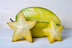 Gwiazdowego jabłka owoc z przyrodnim przekrojem poprzecznym odizolowywającym na drewnianym knurze Zdjęcie Royalty Free