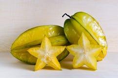 Gwiazdowego jabłka owoc z przyrodnim przekrojem poprzecznym na drewnianym knurze Fotografia Royalty Free