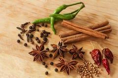 Gwiazdowy anyż, zielony chili, pieprz, cynamon i inne pikantność, - drewniany tło Obraz Royalty Free