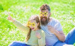Gwiazdowy i sława pojęcie Tata i córka siedzimy na trawie przy grassplot, zielony tło Dziecko i ojciec pozuje z gwiazdą zdjęcie stock