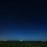 Gwiazdy w nocnym niebie z miastem zaświecają na horyzoncie Ziemia Obrazy Stock