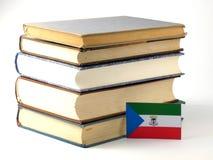 Gwinei Równikowej flaga z stosem książki odizolowywać na bielu plecy obrazy royalty free