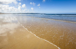 Gwithian Beach, Cornwall. Surf gently breaking on the sandy beach at Gwithian in Cornwall, UK Stock Image
